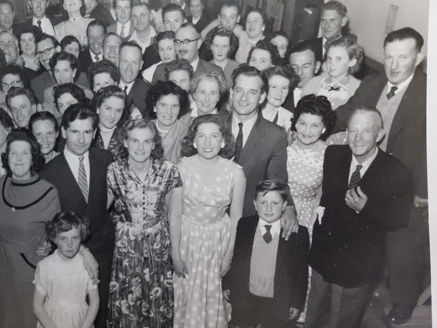 Peggy Martin nee Angerstein at the front with Ernie Martin to the side of her, john their son at the front lady to the right is Florence Angerstein and far right at back is Albert Angerstein