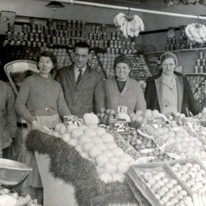'Benwells' the Greengrocers, 2 Furtherwick Parade (now 84 Furtherwick Road) in the late 1950's. L. to R:- not sure, Gladys Payne, Ted Payne, Pauline (Mum's sister), Nora Hart. My Dad worked in the shop after the war, and bought the business when Mrs. Benwell retired in 1957. We moved into the flat above the shop. It later became 'E&K Fruiterers' until 1983, when my Dad became ill and had to retire. It was a great place to live, with Vandersteens Fish & Chip shop on one side, and Grouts the Bakers next door but one. | George Payne
