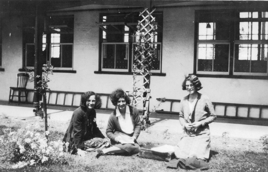 Alma and Louisa Gosling sitting in the quadrangle at school with another teacher centre.