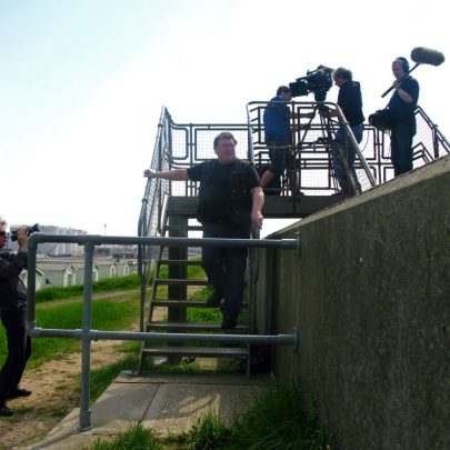 Lobster Smack: Chris Fenwick welcomes the visitors at the location of the 'Down by the Jetty' album whilst Julian Temple (left) films the event for a future documenty film.   (c) David Bullock