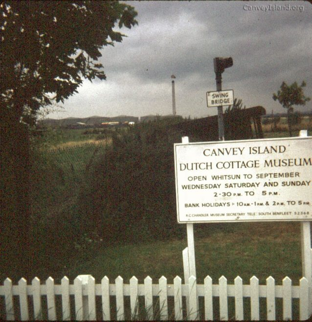 c1980: This photo of the Dutch Cottage Museum sign has an interesting background. The Swing bridge sign and lamp is from the original Canvey Colvin Bridge but is now badly vandalised with the sign missing. Behind you can see the Oil Refinery which has now been demolished. You can also see the oil Refinery chimney which was demolished by Fred Dibnah. | (c) David Bullock