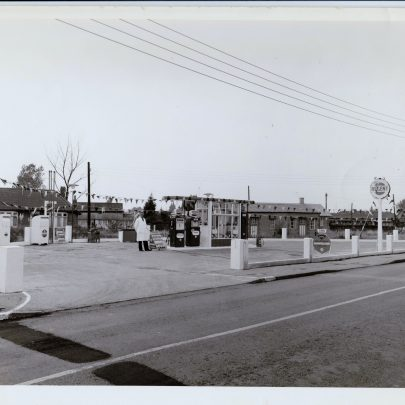Forecourt wide shot showing Marcos Road bungalows behind it and Maurice Road parade in the distance