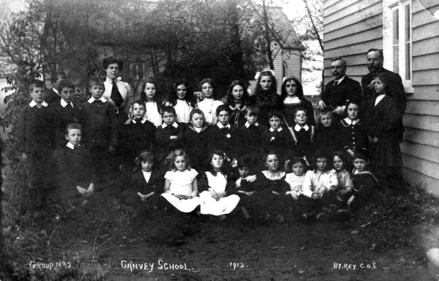 Canvey Village School taken in 1912. I have seen this picture before but the background was unclear. In this copy you can clearly see St Katherine's Church. Lin says her father and his siblings are in this picture but she is not sure which children they are. | Lin and Michael Swanson