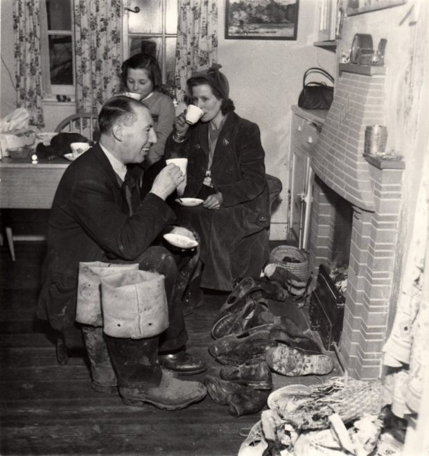 Mr Stanley Davis has a nice hot cup of tea waiting for his wife and little daughter, Susan when they arrived back at their Canvey home which they have before the fire while drying off their sodden boots and shoes.