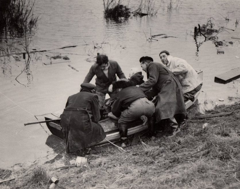 On the back - Rescue workers seen as they carry Mrs Rudge who is nearly 80 years old. She had not eaten since Saturday.   Dated 3rd Feb