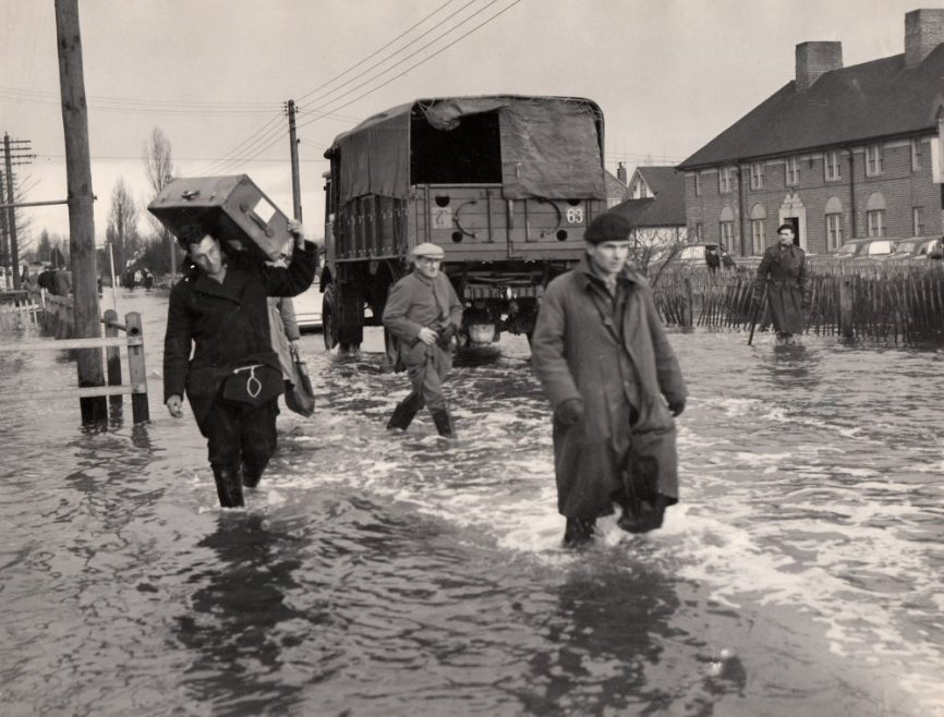 On the back - Flood victims carrying their goods and chattels through the flooded main street. (Long Road by the police station) | Dated 2nd Feb