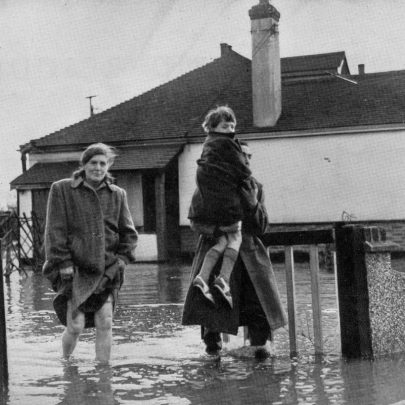 A man and a barefoot woman with a child make their way through flood waters to saftey on Canvey Island, leaving their home under 2 feet of muddy water