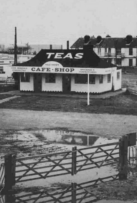 A combined cafe and shop at Hole Haven. Behind it are old terraced timber houses and alongside rows of new caravans; in the far background are gas storage tanks.   Ray Gosling