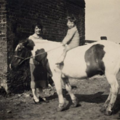 George astride Tim, the pony with his mother holding the reins. | G. Chambers