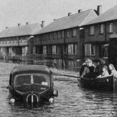 The Avenue, a boat load of rescued people pass between a stranded lorry and van