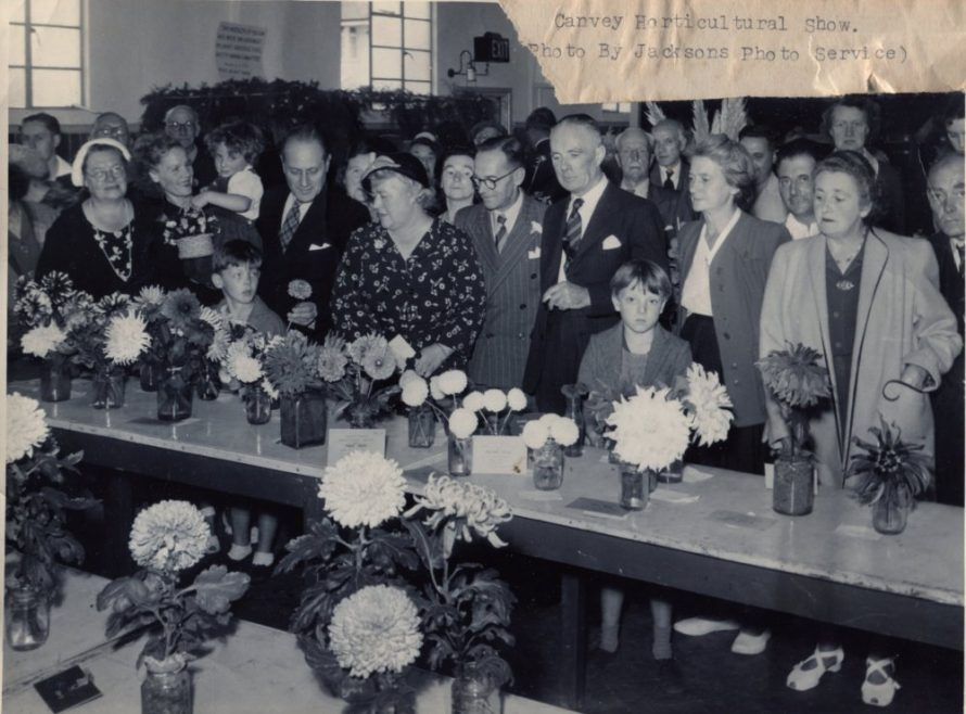 This photo was taken in the mid 1950s probably by Joe Overs. In the centre are CIUDC councillors Mrs Fisk(Con) and Mr Mason(Lab) and to the right are Mrs Hebe Bevan and a young Nigel Bevan. Ah yes! The foreground is full of dahlias. Can anybody identify any of the other people in the picture? | Jacksons Photo Service