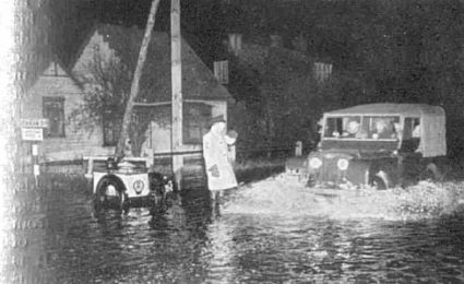 A patrolman directing traffic on the flooded main road of Canvey Island, along which all relief vehicles pass during the initial rescue work on the island