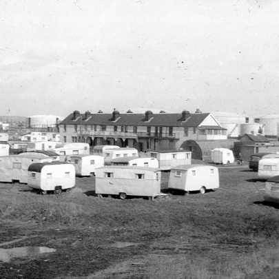 A more familiar scene with the caravans on the land in front of the cottages and the storage tanks behind | Norman Chisman