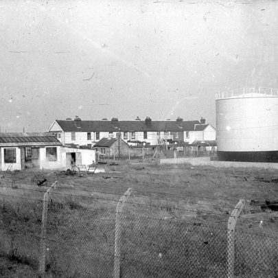 Rear view of the cottages. Looks like the seawall is post 1953 and the tanks are there | Norman Chisman