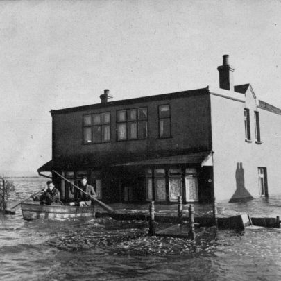 Rescuers continue to search for possible stranded victims at Canvey Island. Here the table floating on its back outside the bungalow is a pathetic reminder that millions of pounds' worth of damage was done by the rising water