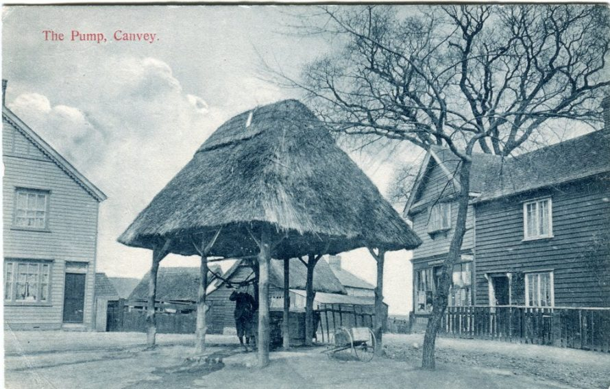 Postcard of the pump dated pre 1918. The Red Cow to the left, Post Office to the right and houses beyond