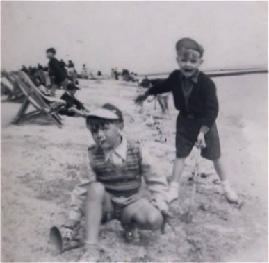 My Dad and his Cousin playing on the beach, the paddling pool in background