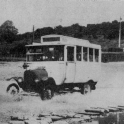 In the early days of Canvey Island bus operation, probably the early 1920s, a Model T Ford, ESH 1504 ( ?), splashes across the Benfleet causeway at low tide