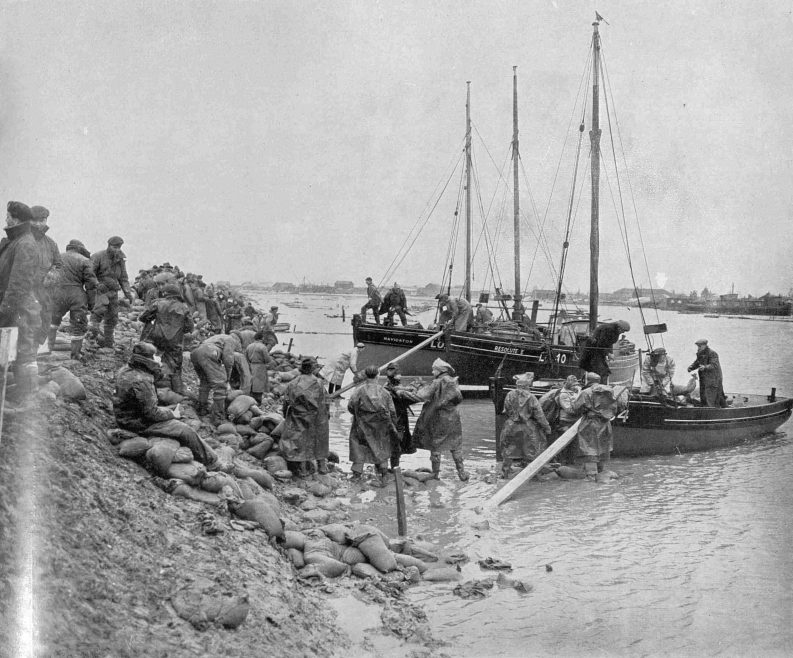 Sandbags are brought by fishing-boats to one of the vital points along the line of Canvey Island's defences : The sandbags are being unloaded along bank runways and troops are waiting on the breached wall to do the stacking. On Tewkes Dyke, one of the main danger-spots at Canvey, no fewer than 600 (service men) were working last week, the force having been built up to this figure when 200 men were drafted from an area where satisfactory progress had been achieved. Admiralty engineer in charge of operations at Canvey has not hesitated to switch men from point to point to keep the work of wall-building going steadily.