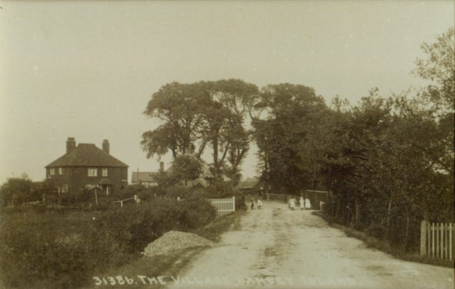 Looking north up Haven Road from what lookslike the entrance to the vicarage. The Red Cow pub can be seen to the left of the trees.