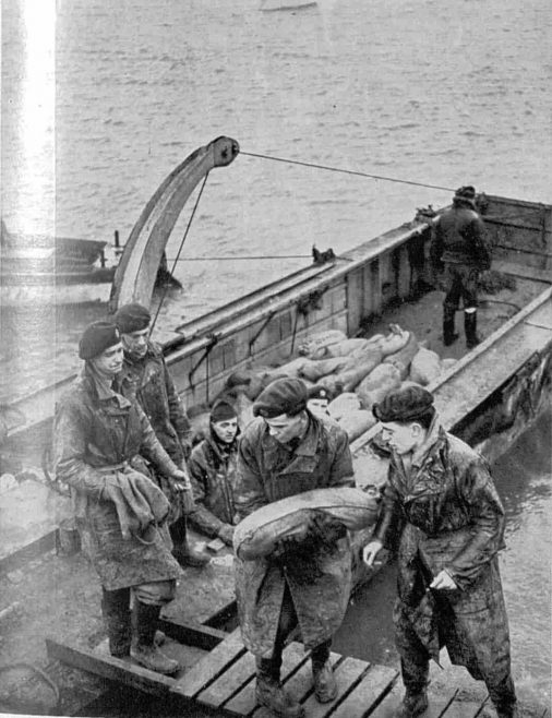 Sandbags passing from hand to hand : Men of the Royal Air Force seen as they filled a barge before it was towed away to the scene of embankment-building at one of the danger-points.