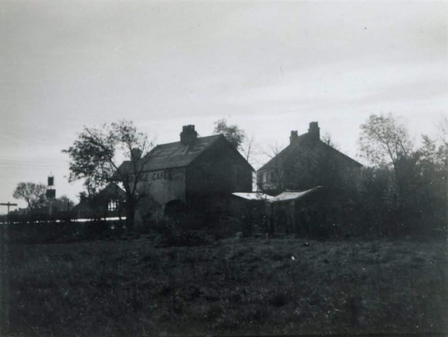 An unusual view of the village taken from behind the shops. You can just make out the Red Cow pub sign on the left and the Orange Cafe in the middle | H Reed
