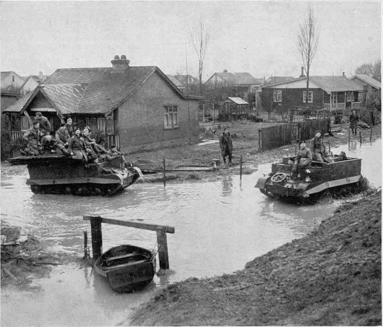 Bren-gun carriers ploughing through the water in a still-flooded Canvey street: The carrier on the left is taking track-laying equipment to the areas where mud has been hampering the work of the troops and civilians engaged in gap-filling. Powerful pumps from volunteer fire brigade organisations have played a big part in reducing the level of the water.