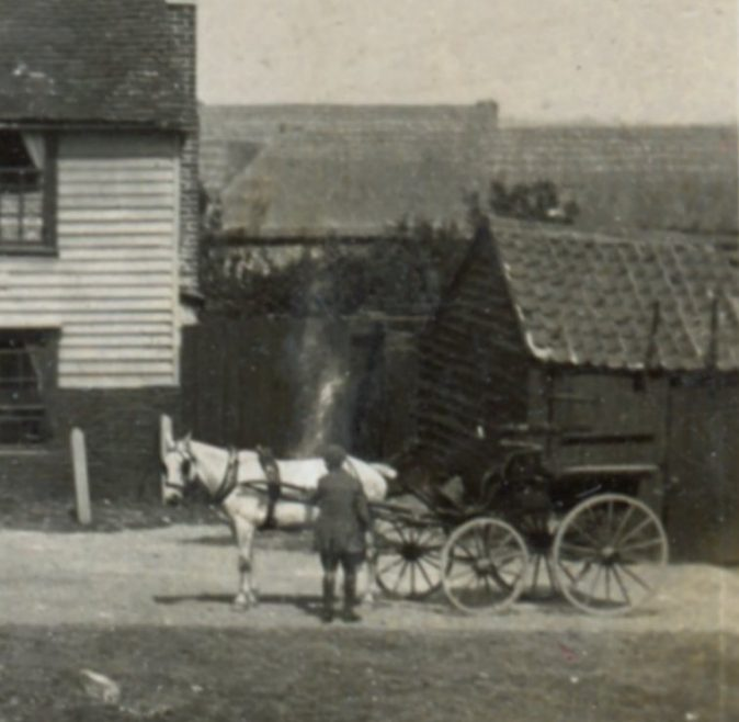 Is that Mr Crow with his carriage waiting to take someone home. The buildings in the back ground would be Sluice Farm