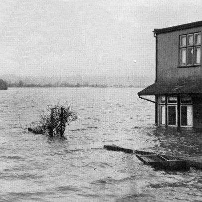 A rescue worker, thigh deep in water, hails a house on Canvey Island in a check-up on residents who might be marooned by the floods