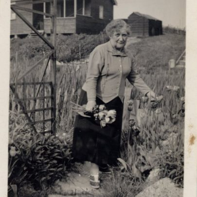 Very clear picture of the grandmother with their bungalow in the background?