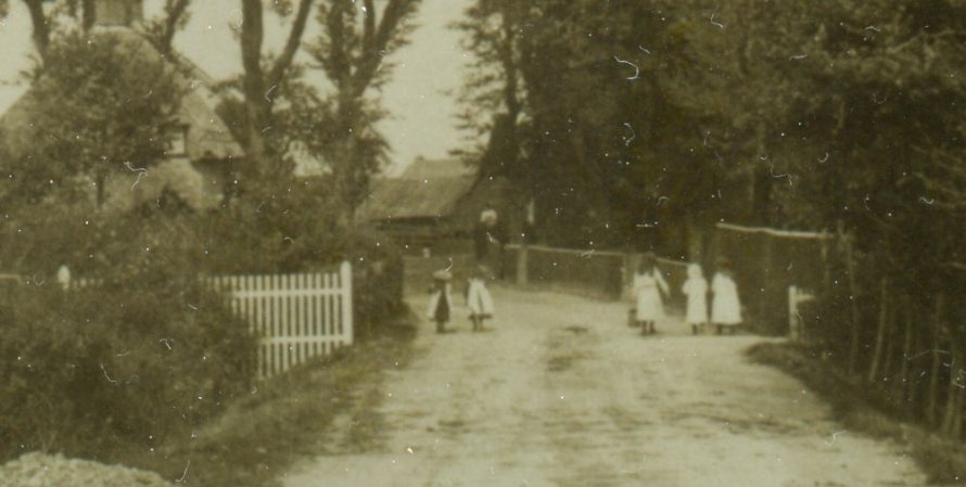 An enlargement of the centre of the postcard showing little children making their way to the pump with their buckets. The 1621 Dutch cottage on the left and in amongst the trees you can just make out the roof of the pump.