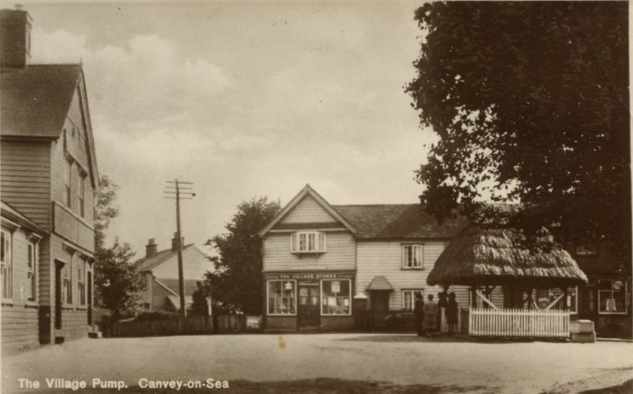 Postcard of the village showing the red Cow public House on the left. The Post office in the middle (these shops are still standing today) and the village Pump
