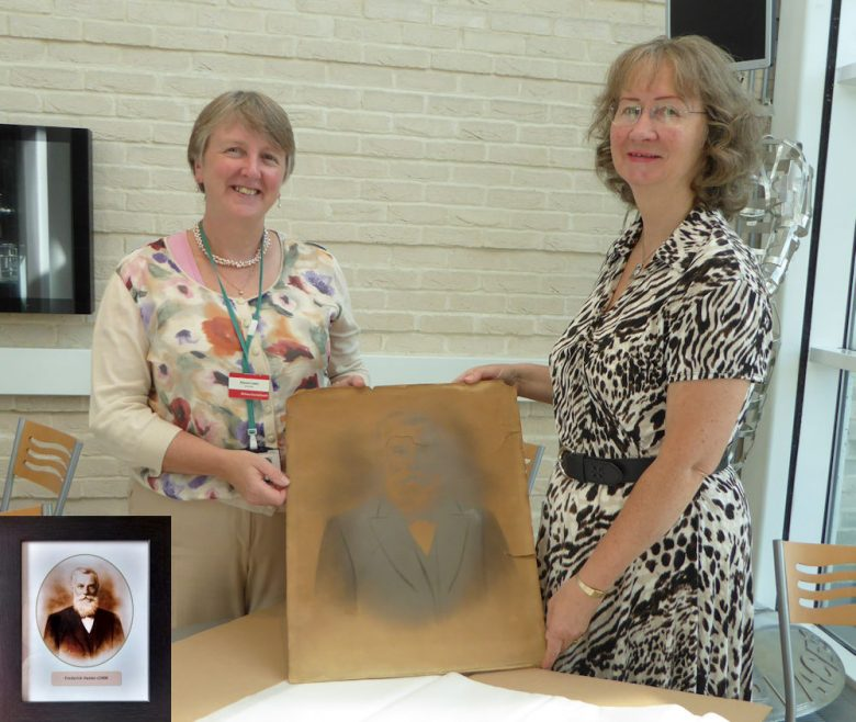 Allyson Lewis, ERO Archivist, accepting the photo from Janet Walden with the reproduced print, bottom left corner, that has been given to the Dutch Cottage Museum.   J Penn