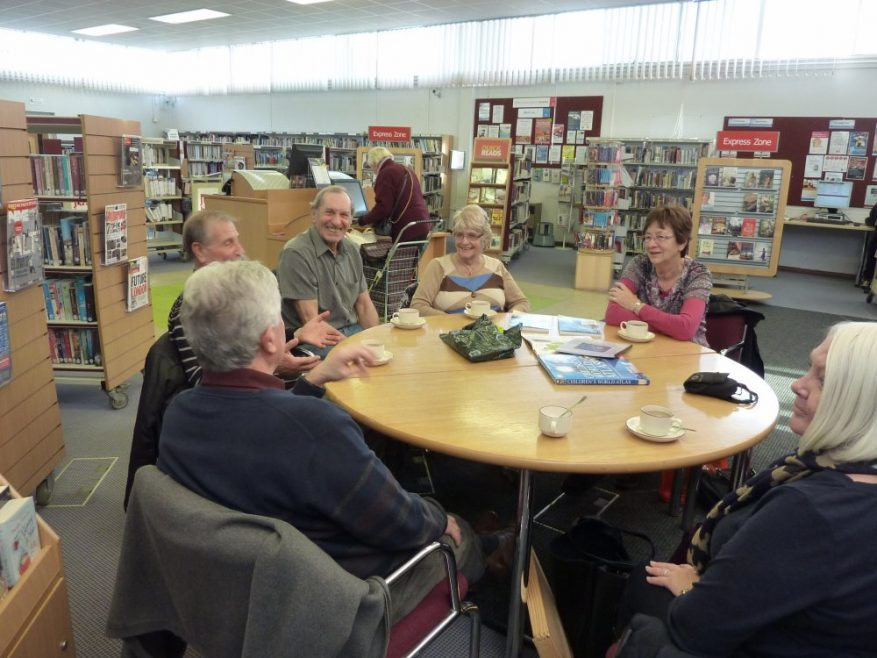 Clockwise - Rod Bishop, Graham Stevens. Brian and Pat Smith, Nellie Verton and Sue Hampson talking about the flood in the library | Janet Penn