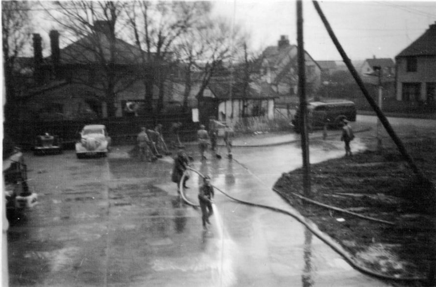 Hosing the mud from the pub forecourt | Carol Frost