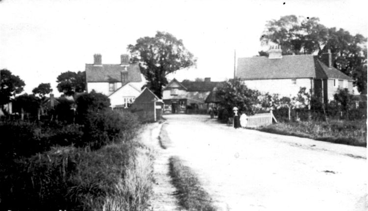 Looking East towards the village. Red Cow on the left, PO in the middle with the pump. Building on the right was later to become the Orange Cafe but at this time was probably run by Scotts. Notice the lady on the right. He outfit shows this is an early card c1900.